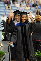 Two students waving to family at hooding ceremony