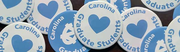 Collection of blue and white buttons saying, 'Carolina Loves Graduate Students'